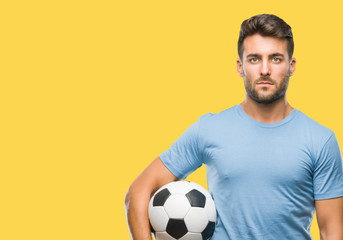 Young handsome man holding soccer football ball over isolated background with a confident expression on smart face thinking serious