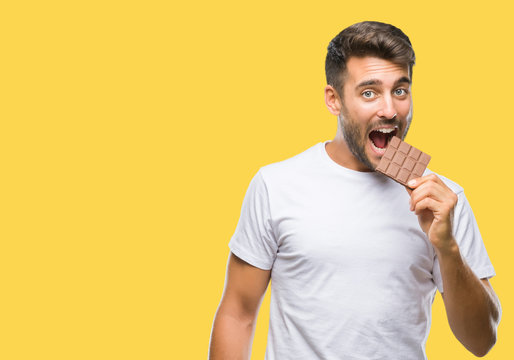 Young handsome man eating chocolate bar over isolated background with a confident expression on smart face thinking serious
