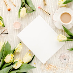 Female workspace with yellow tulip flowers, women's fashion golden accessories, diary,  glasses on white background. Flat lay. Top view feminine background.