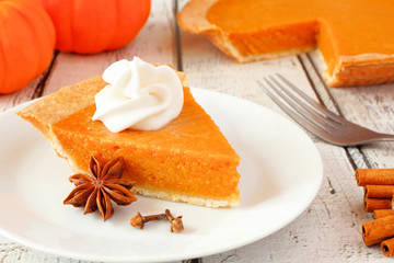 Slice of pumpkin pie with whipped cream. Close up on a white wood background.