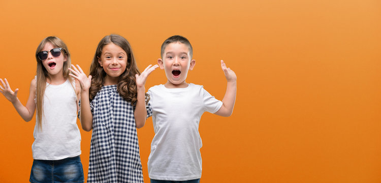 Group of boy and girls kids over orange background very happy and excited, winner expression celebrating victory screaming with big smile and raised hands