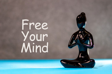 Free your mind - motivating text with white statuette of girl. Yoga and meditation concept