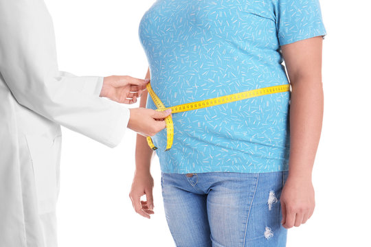Doctor measuring fat woman's waist on white background, closeup. Weight loss
