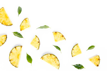 Slices pineapple with green leaves isolated on white background. Flat lay, top view