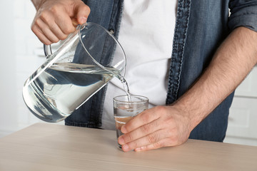 Man pouring water into glass at table, closeup