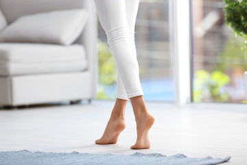 Woman walking barefoot at home. Floor heating
