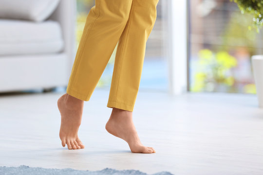 Woman walking barefoot at home, space for text. Floor heating