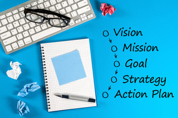 Work place with business process concept - vision - mission - goal - strategy - action plan. On blue background