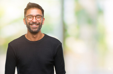 Adult hispanic man wearing glasses over isolated background with a happy and cool smile on face. Lucky person.