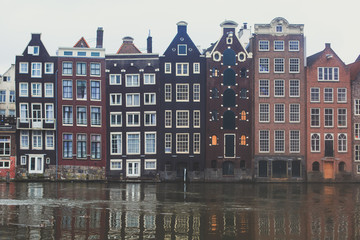"Summer view of the ""Dancing Canal Houses of Damrak' , iconic canal houses in the capital city of Amsterdam, Netherlands"