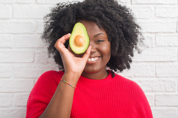 Young african american woman over white brick wall eating avocado with a happy face standing and smiling with a confident smile showing teeth