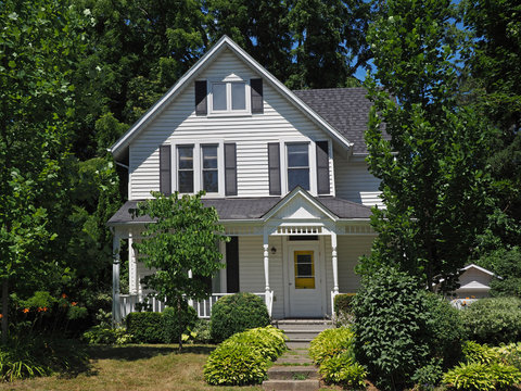 White clapboard house with gable surrounded by trees
