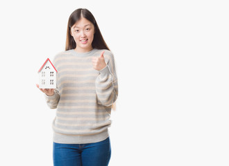 Young Chinese real state agent woman over isolated background holding house happy with big smile doing ok sign, thumb up with fingers, excellent sign