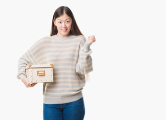 Young Chinese woman over isolated background holding a box screaming proud and celebrating victory and success very excited, cheering emotion