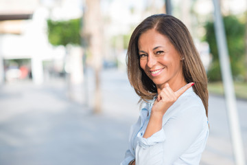Beautiful middle age hispanic woman at the city street on a sunny day very happy pointing with hand and finger to the side