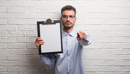 Young adult business man over brick wall holding clipboard pointing with finger to the camera and to you, hand sign, positive and confident gesture from the front