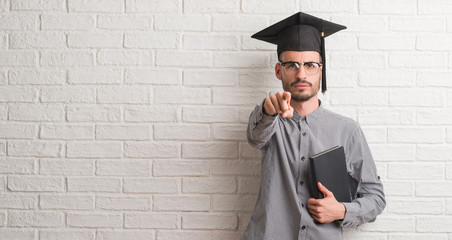 Young adult man over brick wall wearing graduation cap pointing with finger to the camera and to you, hand sign, positive and confident gesture from the front