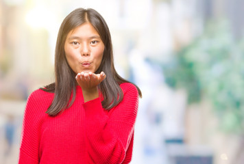 Young asian woman wearing winter sweater over isolated background looking at the camera blowing a kiss with hand on air being lovely and sexy. Love expression.