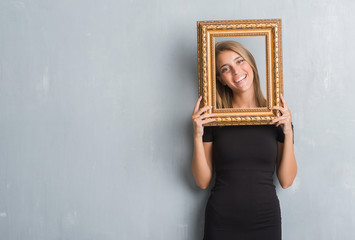 Beautiful young woman over grunge grey wall holding vintage frame with a happy face standing and smiling with a confident smile showing teeth