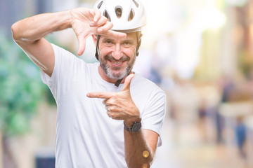 Middle age senior hoary cyclist man wearing bike safety helment isolated background smiling making frame with hands and fingers with happy face. Creativity and photography concept.