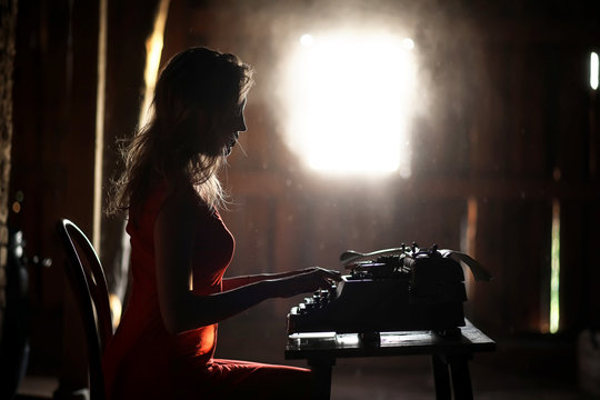 A girl in retro style prints on an old typewriter