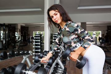 Young attractive woman with slim body pick up dumbbell from equipment rack to do exercise. Morning sport training and physical activity in modern fitness club to keep fit. Healthy lifestyle background