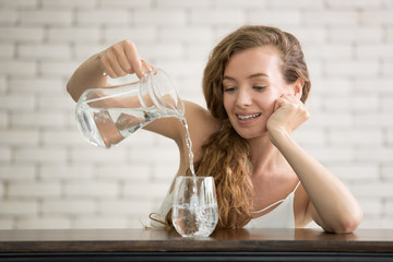 Young woman pouring water from jug into glass in the room