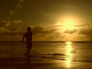 Silhouette of an unrecognizable man throwing out his fishing net from the shore of the Saipan lagoon at sunset, Northern Mariana Islands.