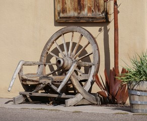 Broken wheels of an old wooden wagon displayed in a backyard
