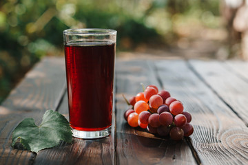 Bunch of red grapes and glass of grape juice on wooden garden table, refreshing organic antioxidant beverage Fototapete