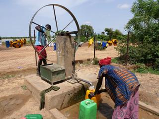 Fototapeta donna africana raccoglie l'acqua al pozzo  obraz