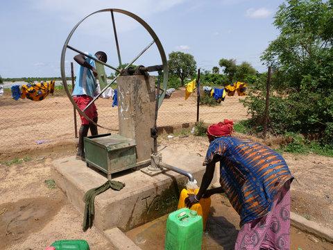donna africana raccoglie l'acqua al pozzo