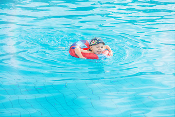 little boy swims, cheerful child jumping in the pool in the circle, open-air swimming pool,