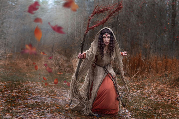 a witch in rags conjures in forest