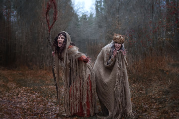 two witches in rags in forest