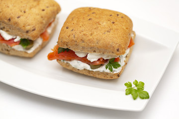Sandwich with salmon, cheese and cereal bread on white background. Close up.