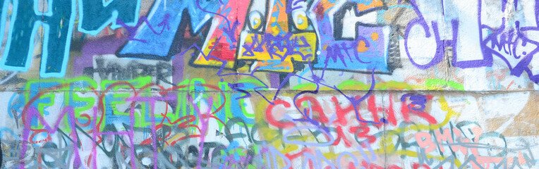 Fragment of graffiti tags. The old wall is spoiled with paint stains in the style of street art...