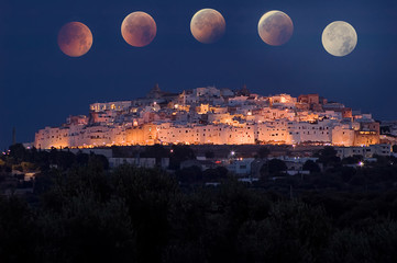 Ostuni in the night, the white city in Apulia, with total eclipse