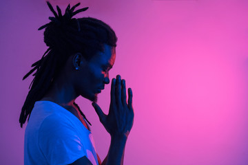 Close up of silhouette African man with dreadlocks praying on purple background