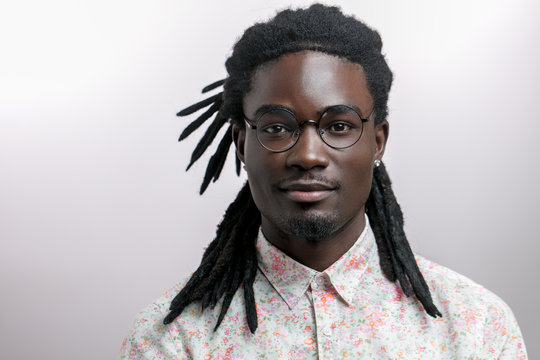 young handsome afro american man with dreadlocks isolated on white background