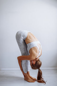 Young woman with ponytail hair, practicing yoga, standing forward bend exercise, head to knees, wearing sportswear, white studio background
