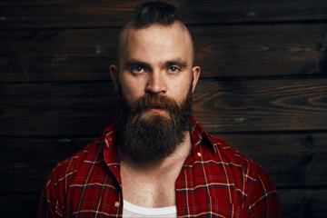 Caucasian male with beard and mohawk, dressed in checkered red shirt