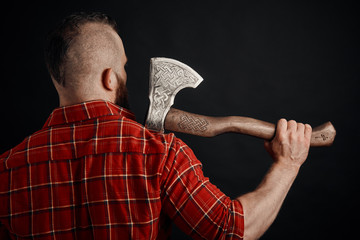 rear view of bearded mohawk man with axe on shoulder in studio
