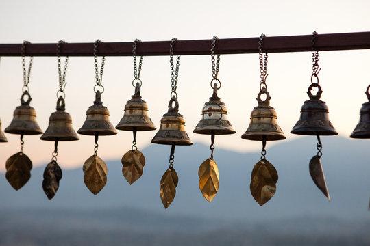 Prayer Bells at Svayambunath Stupa in Kathmandu, Nepal with Himalayas on background at sunset