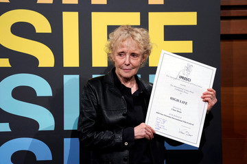 French director Claire Denis holds up her Fipresci Award at the San Sebastian Film Festival