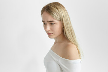 Sideways studio picture of beatiful serious young woman with straight hair posing isolated, frowning, having absent-minded facial expression, thinking over some problem. Nervousness and uneasiness