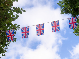 Red, white and blue festive bunting flags against sky background. Union Jack, UK flags. Brexit maybe.