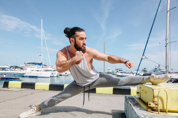 Sports lifestyle. Cheerful determinated young caucasian bodybuilder with stylish hair bun and beard stretching on the sea shore.