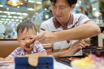 Asian Father feeding food to cute little Asian 2 years old toddler boy child while watching smartphone at restaurant, Toddlers and mealtime manners, Leisure & technology & internet addiction concept