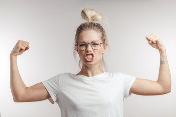 I can everything. Happy young blonde woman in white t-shirt showing biceps on her arms. Emotional portrait with white background of expressive girl with blonde hair bun and spectacles.